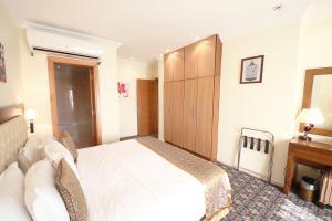 Cama ou camas em um quarto em Al Rabitah Al Fondoqeiah Hotel Apartments