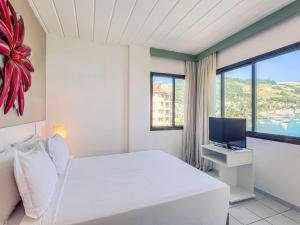 A bed or beds in a room at Mercure Angra dos Reis