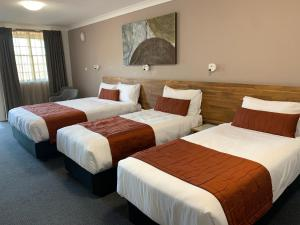 A bed or beds in a room at In Town Motor Inn