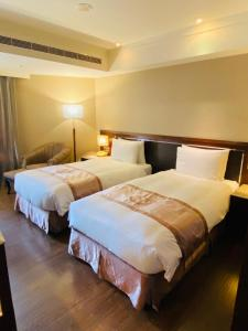 A bed or beds in a room at Taichung Charming City Hotel