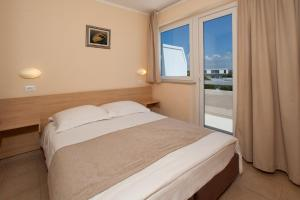 A bed or beds in a room at Hotel Delfin Plava Laguna