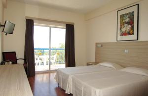 A bed or beds in a room at Marina Hotel