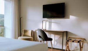 Uma televisão e/ou sistema de entretenimento em Monte Prado Hotel & Spa