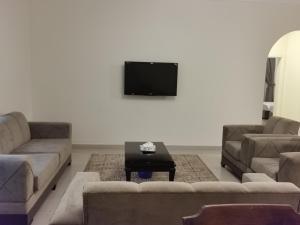 Uma TV ou centro de entretenimento em Al Fakhama Al Momaiza Hotel Suites