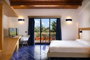 A bed or beds in a room at Magaggiari Hotel Resort