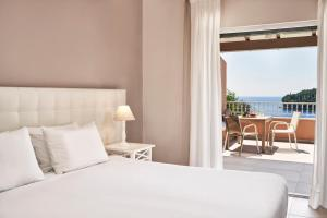 A bed or beds in a room at San Antonio Corfu Resort (Adults Only)
