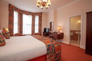 A bed or beds in a room at Arundel House Hotel