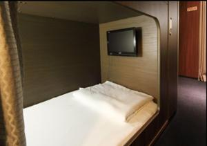A bed or beds in a room at Capsule Hotel Nikoh Refre(Male Only)