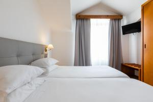 A bed or beds in a room at Hotel Arcanjo