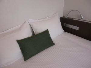 A bed or beds in a room at Y's HOTEL Shin Osaka