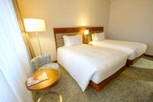 A bed or beds in a room at Hilton Garden Inn Mbabane