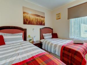 A bed or beds in a room at Thistle Dhu Guest House