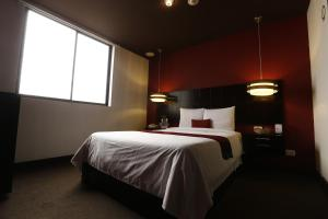 A bed or beds in a room at Hotel Ginebra