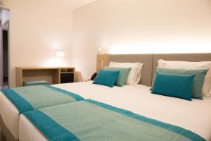 A bed or beds in a room at Mafra Hotel