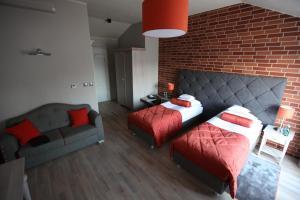 A bed or beds in a room at Hotel Browar Kościerzyna