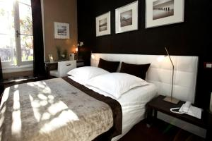 A bed or beds in a room at Hotel des Arceaux