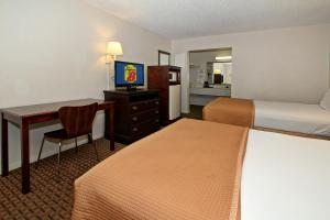 A bed or beds in a room at Super 8 by Wyndham Kissimmee