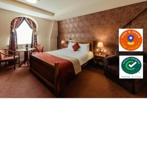 A bed or beds in a room at Carnegie Court Hotel