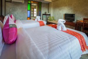 A bed or beds in a room at Rainforest ChiangMai Hotel