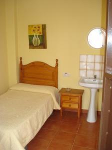 A bed or beds in a room at Pensión Bienvenido