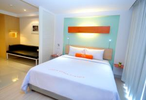 A bed or beds in a room at Hotel & Residences Riverview Kuta - Associated HARRIS