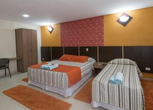 A bed or beds in a room at Monte Serrat Hotel