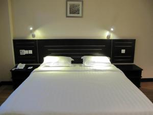 A bed or beds in a room at Labuk Hotel