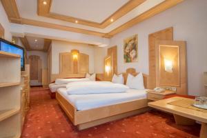 A bed or beds in a room at Alphotel Garni Salner