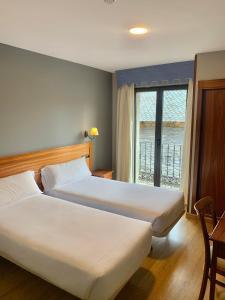 A bed or beds in a room at Hotel Los Templarios