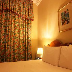 A bed or beds in a room at The Windermere Hotel, London