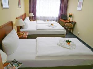 A bed or beds in a room at Hotel Amadeus Central