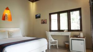 A bed or beds in a room at Puri Rinjani Bungalows