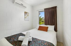 A bed or beds in a room at Kurrimine Beach Huts