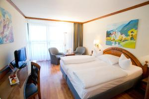 A bed or beds in a room at Riessersee Hotel