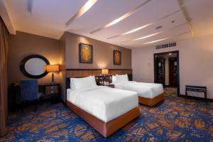 سرير أو أسرّة في غرفة في فندق صفوة الغفران مكة