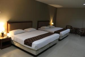 A bed or beds in a room at Hotel Palm Inn Butterworth
