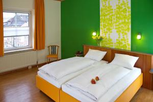 A bed or beds in a room at Stadtcafé Hotel garni