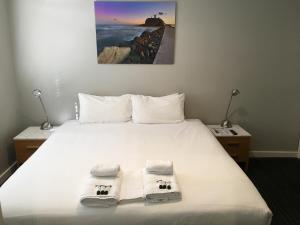 A bed or beds in a room at The Premier Hotel Broadmeadow