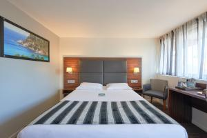 A bed or beds in a room at Kyriad Bordeaux - Merignac Aéroport