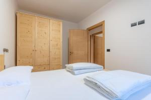 A bed or beds in a room at Dolomitissime Holiday Homes Alleghe