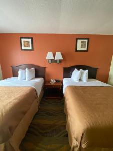 A bed or beds in a room at Travelodge by Wyndham La Porte/Michigan City Area