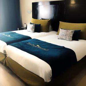 A bed or beds in a room at Palm Plaza Hôtel & Spa