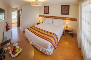 A bed or beds in a room at Taypikala Hotel Cusco