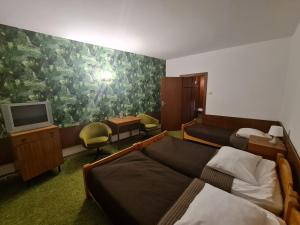 A bed or beds in a room at Zespół Tatry - Hotel Tatry i Budynek Turystyczny