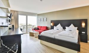 A bed or beds in a room at Strandhotel Bene