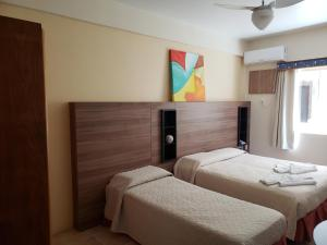 A bed or beds in a room at De Rose Praia Hotel