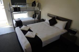 A bed or beds in a room at Dooley's Tavern & Motel Springsure