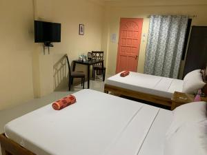 A bed or beds in a room at Susada's Inn
