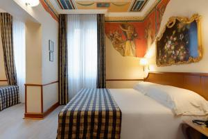 A bed or beds in a room at Hotel Amalfi