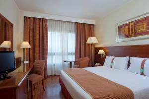 A bed or beds in a room at Holiday Inn Cagliari, an IHG Hotel